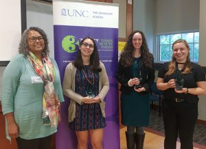 Four women, three holding trophies, stand in front of the Three Minute Thesis banner.